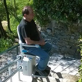 persona sale con il montascale a poltroncina curvilineo da esterno