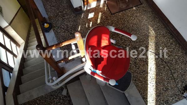Poltroncina rossa di montascale curvilineo a doppia guida in edificio di Ceranesi