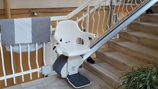 Montascale con poltroncina bianca modello rettilineo da esterno presso casa di Diano Marina