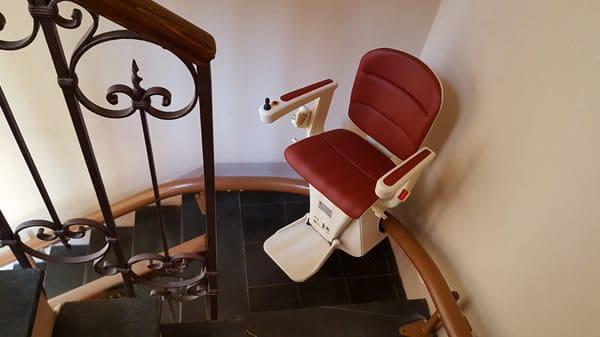 Montascale con poltroncina rossa modello curvilineo monoguida in appartamento di Gavi