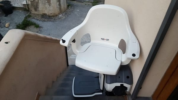 Poltroncina bianca di montascale rettilineo da esterno in appartamento di Genova Rivarolo