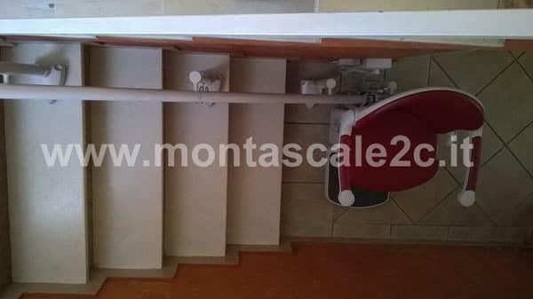 Montascale curvilineo a doppia guida con poltroncina rossa in casa di Mondovi