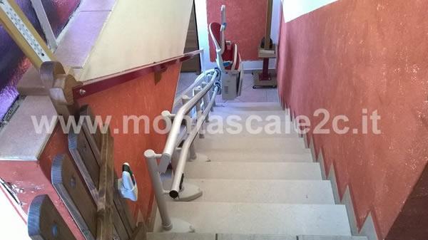 Foto di scalinata con rotaia e montascale curvilineo a doppia guida in edificio di Mondovi