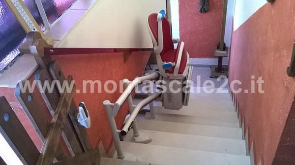Montascale con poltroncina rossa , modello curvilineo a doppia guida installato da Montascale 2C in edificio di Mondovi