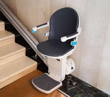 Montascale con poltroncina di colore scuro pronto per essere utilizzato da persone con disabilità