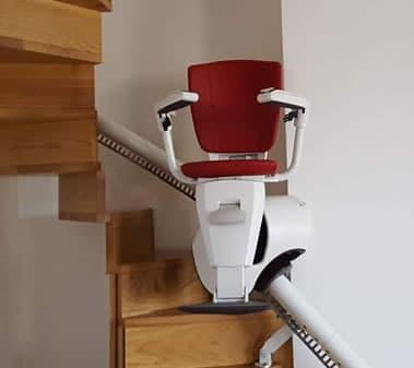 Montascale con poltroncina rossa durante la salita su scala a chiocciola
