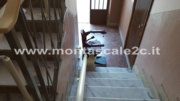 Foto di un montascale a poltroncina curvilineo monoguida realizzato dalla ditta Montascale 2c ed installato presso un palazzo di Asti