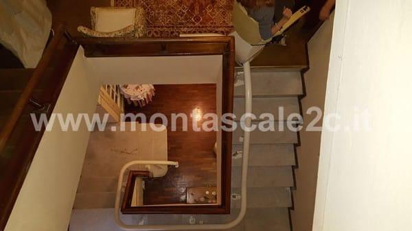 Foto delle scale con installato un montascale a poltroncina curvilineo monoguida realizzato dalla ditta Montascale 2c