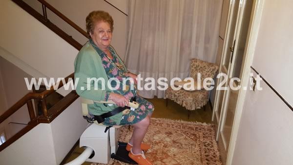 Signora anziana mentre sale le scale grazie all'utilizzo di un montascale a poltroncina curvilineo monoguida ideato dalla ditta Montascale 2c