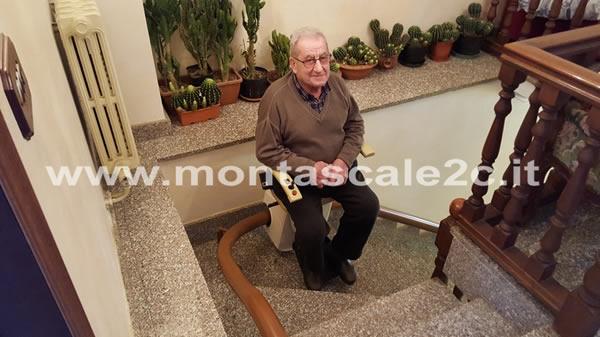 Foto di signore anziano che può salire le scale grazie all'utilizzo di un montascale a poltroncina curvilineo monoguida ideato dalla ditta Montascale 2c