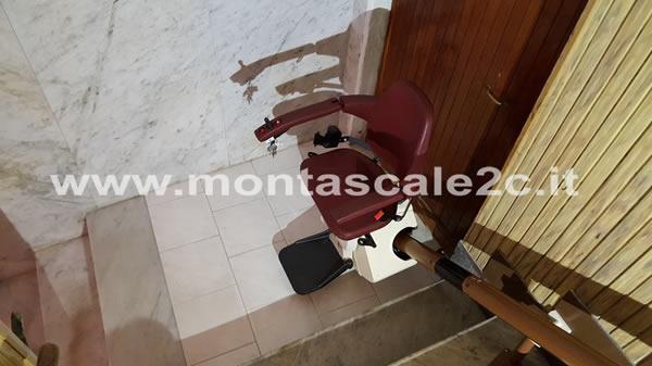 Montascale a poltroncina curvilineo monoguida realizzato dalla ditta Montascale 2c ed installato presso un palazzo di Genova Pontedecimo