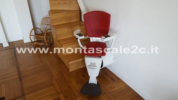 Foto con particolare sulla poltroncina rossa di un montascale curvilineo monoguida installato presso un appartamento di Genova Principe