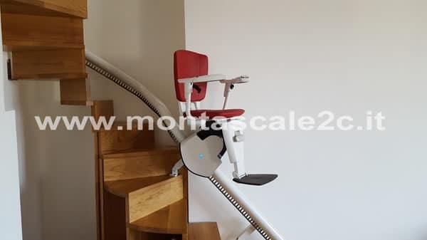 Particolare di un Montascale con poltroncina rossa, modello curvilineo monoguida della ditta Montascale 2c ed installato all'interno di un palazzo situato a Genova Principe