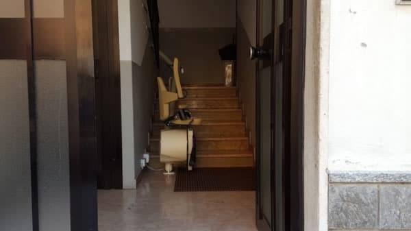 Ingresso di una casa di Piacenza con alla base delle scale installato un modello di montascale curvilineo monoguida