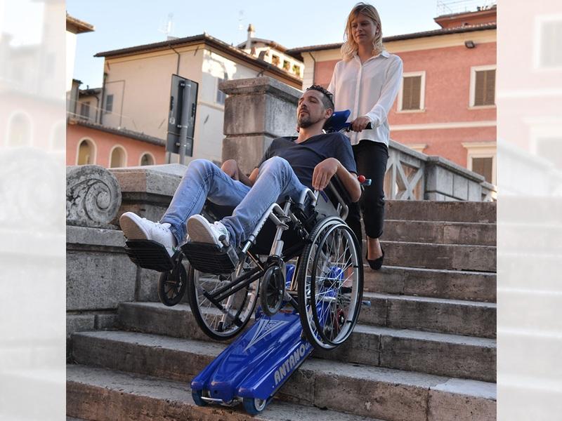 disabile supera una scalinata con l'ausilio di un montascale a cingoli